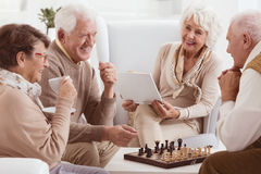 Pensioners playing chess. Happy pensioners of rest home playing chess stock photography