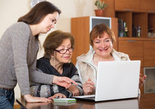 Pensioners and relative working on laptop Royalty Free Stock Photography