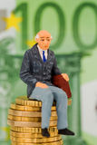 Pensioners sitting on cash pile Royalty Free Stock Photography