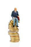 Pensioners sitting on a pile of money. Symbolic photo for pension, retirement, old-age security Royalty Free Stock Photography