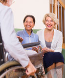 Pensioners visiting disabled friend Stock Images
