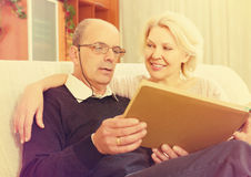 Pensioners watching old photoes Royalty Free Stock Photos
