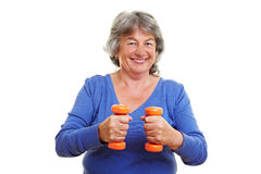 Pensionier exercising. Elderly woman exercising with two small dumbbells Royalty Free Stock Photos