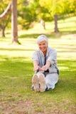 Pensionierte Frau, die sie Ausdehnungen tut Stockfoto