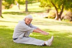 Pensionierte Frau, die sie Ausdehnungen tut Stockbilder