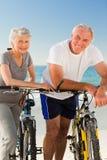 Pensionierte Paare mit ihren Fahrrädern auf dem Strand Lizenzfreies Stockfoto