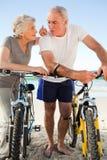 Pensionierte Paare mit ihren Fahrrädern auf dem Strand Lizenzfreie Stockfotografie