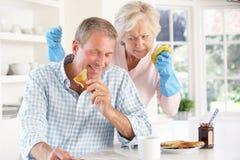 Pensionierter Mann, der nicht bei der Hausarbeit hilft Lizenzfreie Stockbilder