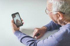 Pensionierter Mann unter Verwendung der Computertechnologien zu Hause stockfoto