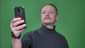 Pensionista caucásico rubio en el jersey gris que toma las selfie-fotos en smartphone en fondo verde metrajes