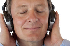 Pensionista com auscultadores que escuta a música mp3 Fotografia de Stock Royalty Free