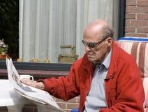 Pensionista con las gafas de sol que lee el periódico i Foto de archivo libre de regalías