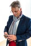 Pensionista elegante que comprueba su teléfono móvil Imágenes de archivo libres de regalías