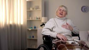 Pensionista en el dolor de pecho de la sensación de la silla de ruedas, ataque del corazón, infarto del miocardio fotografía de archivo libre de regalías
