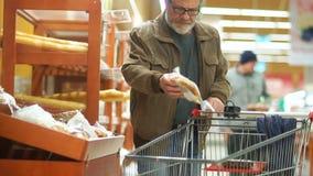 Pensionista en el supermercado Rolls el carro al departamento del pan, elige un bollo fresco Alimento sano almacen de video