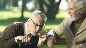 Pensionista envejecido con problema de la audiencia que escucha el amigo, sentándose en banco de parque almacen de video