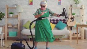 Pensionista feliz alegre de la mujer mayor con el pelo gris en los vidrios que juegan un aspirador como una guitarra MES lento almacen de metraje de vídeo