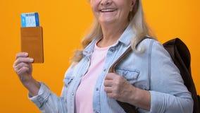 Pensionista femenino con el pasaporte y el boleto en manos, viaje de la tenencia de la mochila almacen de video