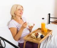 Pensionista femenino con el zumo, las bayas y el yogur de naranja Foto de archivo