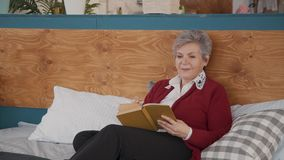 Pensionista femenino jubilado relxing en libro de la ficción de la lectura del dormitorio almacen de video