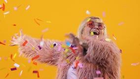 Pensionista femenino moderno que disfruta del festival debajo de confeti colorido que cae, diversión almacen de video