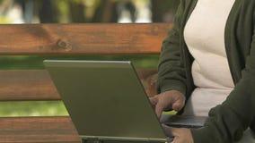 Pensionista femenino que mecanografía en el ordenador portátil, parque que se sienta, conexión pública del punto de Wi-Fi metrajes