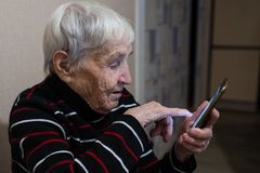 Pensionista idoso idoso da mulher que datilografa em um smartphone ajuda imagens de stock royalty free
