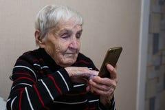 Pensionista idoso idoso da mulher que datilografa em um smartphone imagem de stock