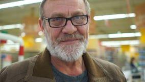 Pensionista maduro en el supermercado, retrato cercano, sonrisa triste El hombre tiene una barba gris aseada, los ojos y óptico a metrajes