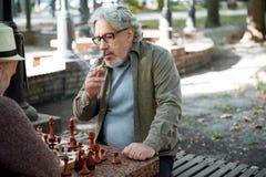 Pensionista masculino mayor que piensa en próximo paso en juego de ajedrez Fotos de archivo