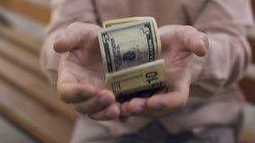 Pensionista masculino pobre que muestra pocos billetes de dólar en las manos, crisis económica, necesidad almacen de metraje de vídeo