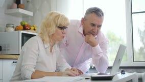 Pensionista masculino que enseña a la esposa jubilada a utilizar el ordenador portátil en cocina moderna metrajes