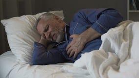 Pensionista masculino que tem o cardíaco de ataque, dor no peito afiada de sofrimento ao dormir fotografia de stock royalty free