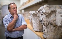 Pensionista masculino que visita a exposição histórica no museu fotografia de stock royalty free