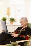 Pensionista moderno con la computadora portátil Imágenes de archivo libres de regalías