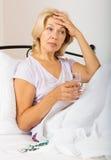 Pensionista na cama com comprimidos e vidro da água Foto de Stock Royalty Free