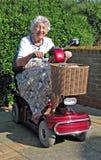 Pensionista que demuestra la vespa de la movilidad Imagenes de archivo