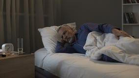 Pensionista que espera impacientemente a manhã para vir, insônia de sofrimento na noite imagem de stock royalty free