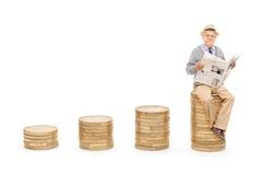 Pensionista que lee las noticias en una pila de monedas Foto de archivo libre de regalías