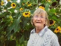 Pensionista sonriente en su jardín con el girasol Imágenes de archivo libres de regalías
