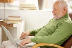 Pensionista sonriente que usa el ordenador portátil imagen de archivo libre de regalías
