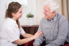 Pensionista y cuidador sonrientes imágenes de archivo libres de regalías