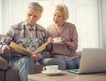 Pensionistas casados que leen el documento junto fotografía de archivo
