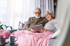 Pensionistas encantadores sinceros que descansan en casa con el libro Imágenes de archivo libres de regalías