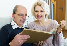 Pensionistas felices que miran viejos photoes Imagen de archivo libre de regalías