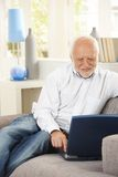 Pensionné gai à l'aide de l'ordinateur portatif sur le divan Photographie stock libre de droits