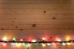 Pensionnaire de lumière de Noël sur le fond en bois Photographie stock