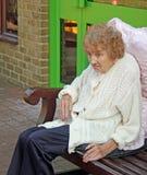 Pensionär, der A auf Bank sitzt Stockbild