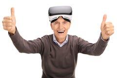 Pensionär som ger tummar, upp når att ha använt en VR-hörlurar med mikrofon Royaltyfri Foto