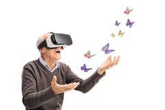 Pensionär som visualiserar fjärilar via VR-hörlurar med mikrofon Fotografering för Bildbyråer